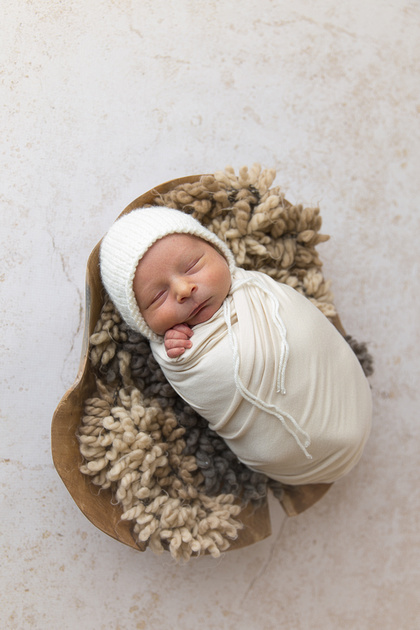 Wrapped Newborn photographed in wooden bowl