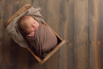 Newborn Baby Boy in Wooden Bed