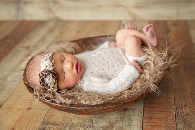 Newborn Baby Girl Posed in Natural Wooden Bowl